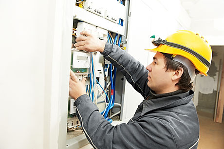 electrician builder at work installing energy saving meter into electric line distribution fuseboard