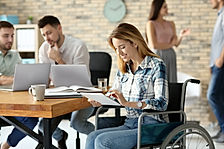Young woman in wheelchair and colleagues