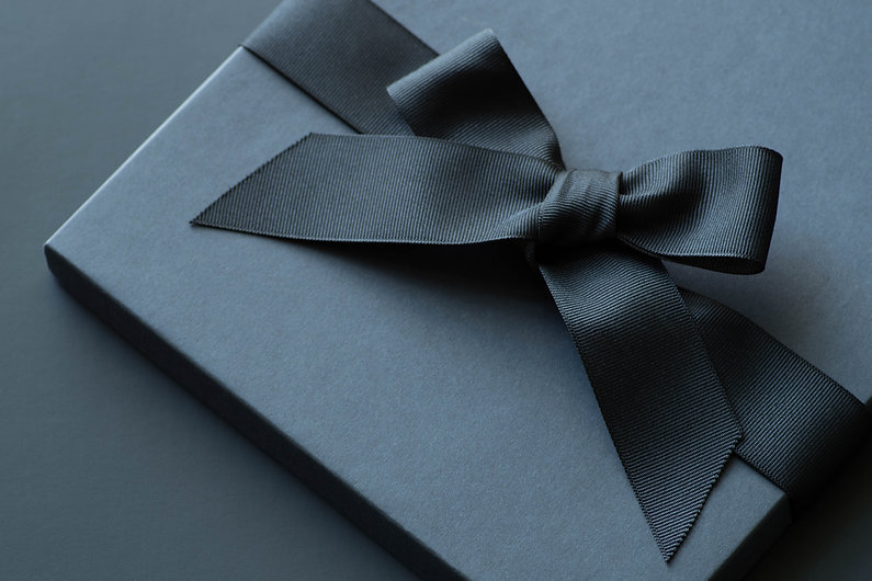 Black gift box on a dark contrasted back