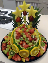 Watermelon fruit basket filled with kiwi, red ang reen seedless grapes, strawberries and pineapples