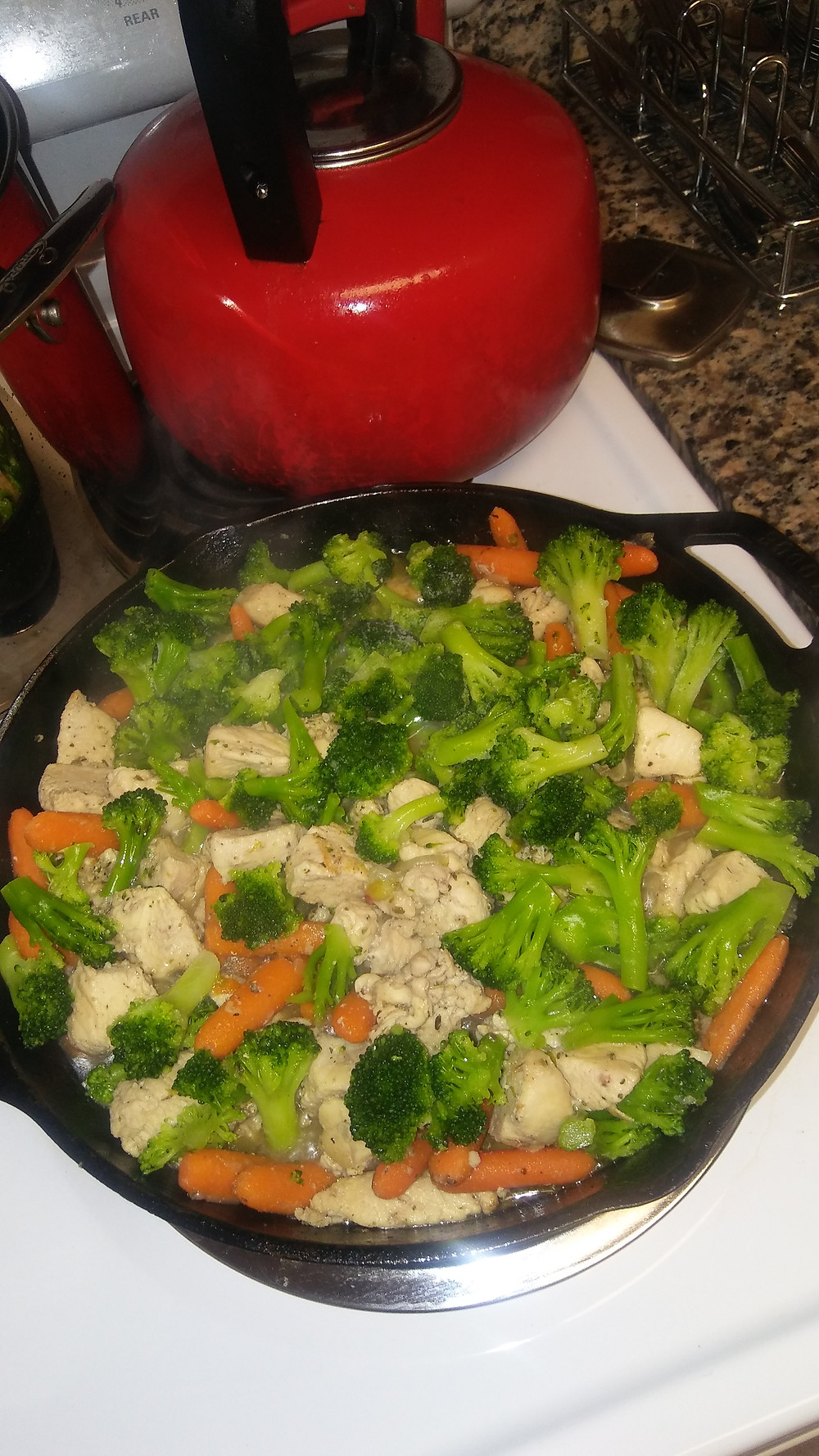 Chicken and vegetable stir fry with carrots, broccoli, and herbs