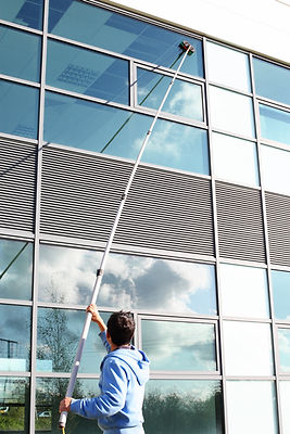 Glass on a commercial building being cleaned after they were replaced