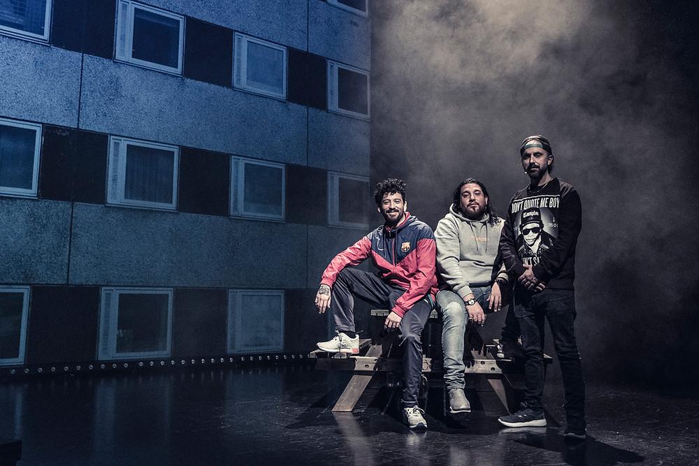 Skuespillerne og rapperne Fela, Castro og Don Martin sitter på en benk på scenen under forestillingen Blokk til Blokk.