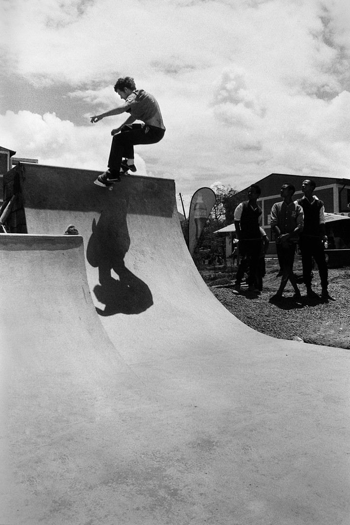 Josh of the UK front smith the quarter pipe as three local youth watch live skateboarding for the very first time.