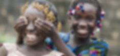 African Girls Playing Peekaboo Outdoors