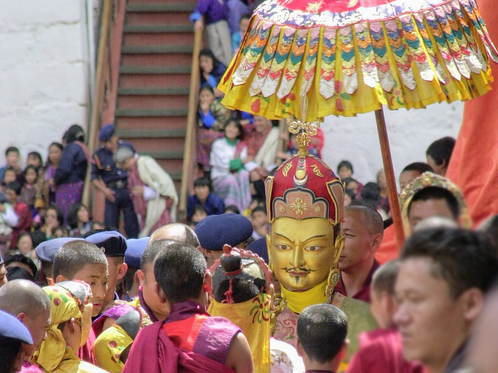 Sheltered under silken parasols, the beatific Guru Padmasambhava (in a gold mask) arrives in a procession ahead of the Dance known as the Eight Names of Padmasambhava, or Guru Tshen Gye. Mask Dance of Bhutan.