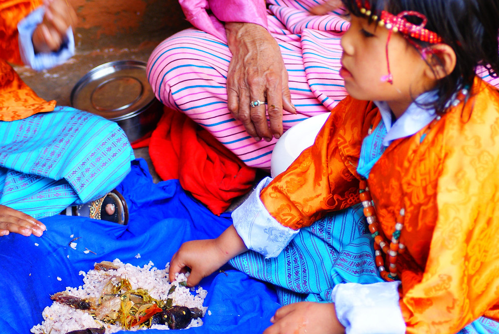 A Bhutanese girl in traditional finery enjoying her celebratory new year meal.