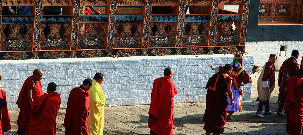 The yellow-robed figure of Bhutan's highest Buddhist monk, the Je Khenpo, leads a traditional procession at the Punakha festival in Bhutan. Copyright, Bhutan Himalaya Expeditions