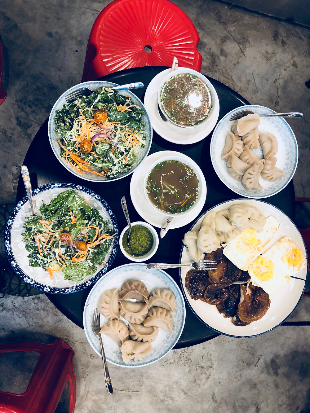 A selection of traditional and modern Bhutanese eats, including momos or steamed dumplings, bone broth, fried eggs and wild shiitake.