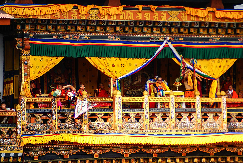 Covered in gold and silk fabrics, the upper gallery of the Punakha Dzong is occupied by dignitaries at the Punakha Festival. Copyright, Bhutan Himalaya Expeditions