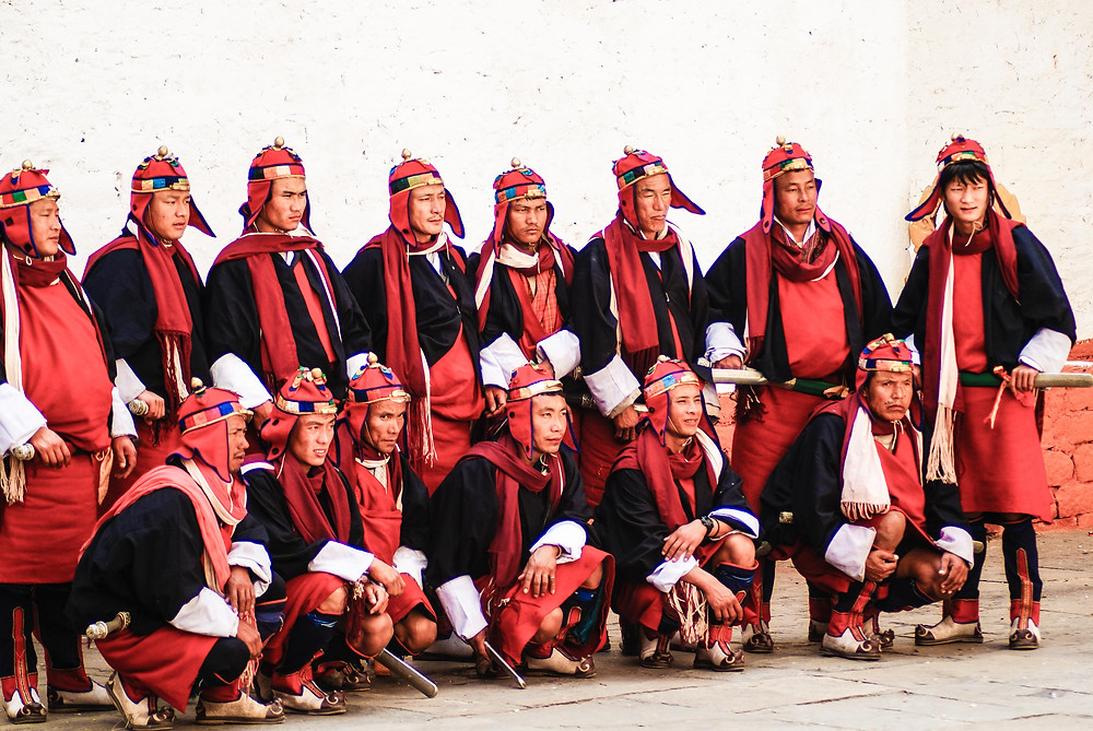 A line-up of Bhutanese warriors at the Punakha Festival, in helmets, wearing swords and dressed in their bright red uniform woven from yak-hair