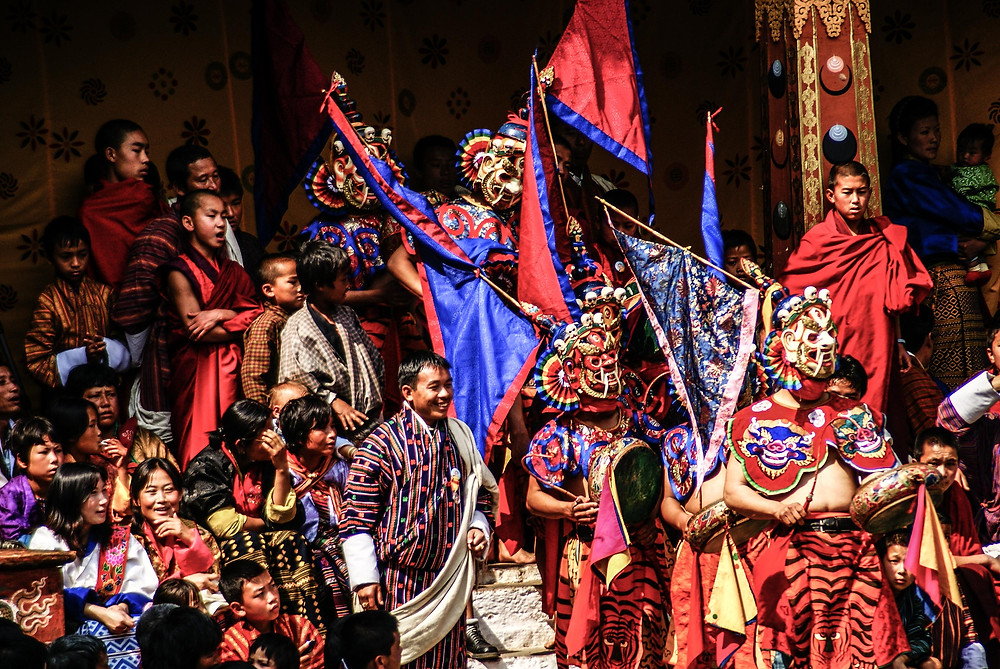 Mask Dancers in a blaze of red and blues, preparing to perform at the Punakha Festival in Bhutan. Copyright, Bhutan Himalaya Expeditions
