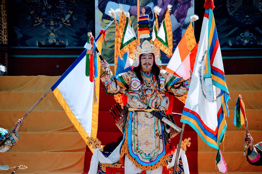 A senior lama in the titular role of King Gesar of Ling wears a golden crown, royal robes, and carries multi-colored triangular flags symbolizing the colors of Himalayan Buddhist kings.