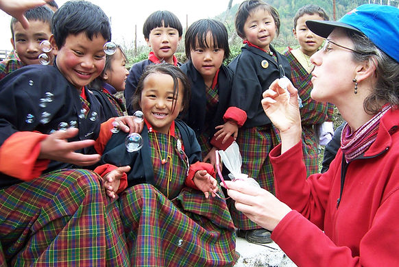 Bhutan Himalaya Expeditions guest blowing bubbles with laughing Bhutanese children