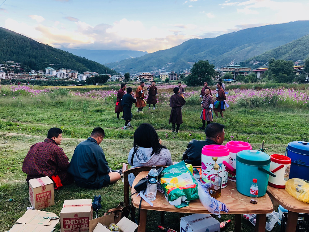 Bhutanese men celebrate the new year playing archery and throwing darts while family members act as audience and cheering squad.
