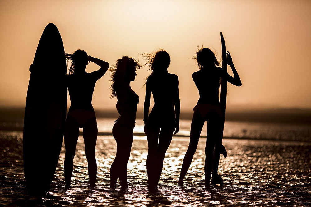 the silhouettes of Amadeus Electric Quartet girls in the sun set with surfing boards