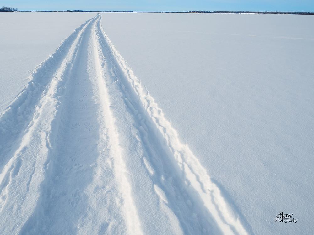 snowy scene, frozen lake, snowmobile tracks