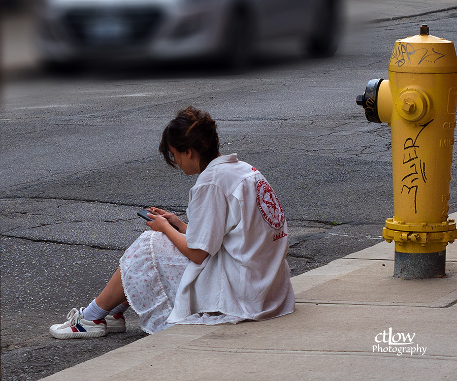 Young woman on curb on work-break