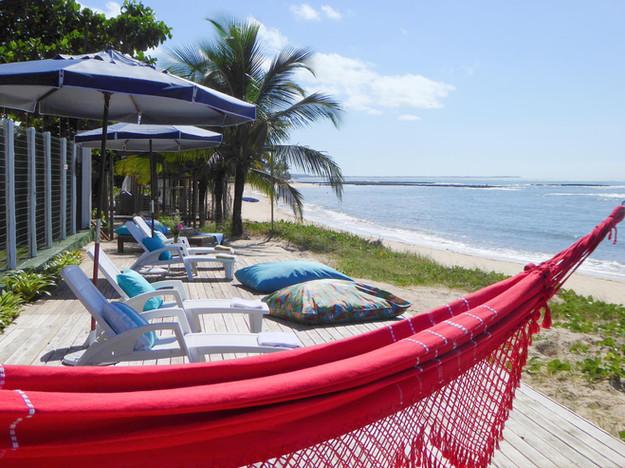 nosso deck na praia, com estrutura para que passe um dia confortável na beira do mar. tem à sua disposição espreguiçadeiras, almofadas, redes, sombra com guarda sol