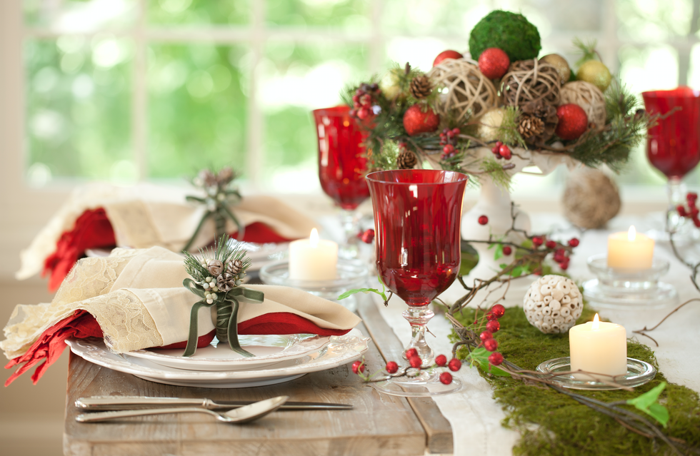 Linen table runner and napkins are set off beatifully by red glasses and berries and the moss table runner adds touch of nature which goes well with the christmas table centre piece.