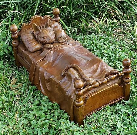 Cat asleep in a bed sculpture by Deran Wright