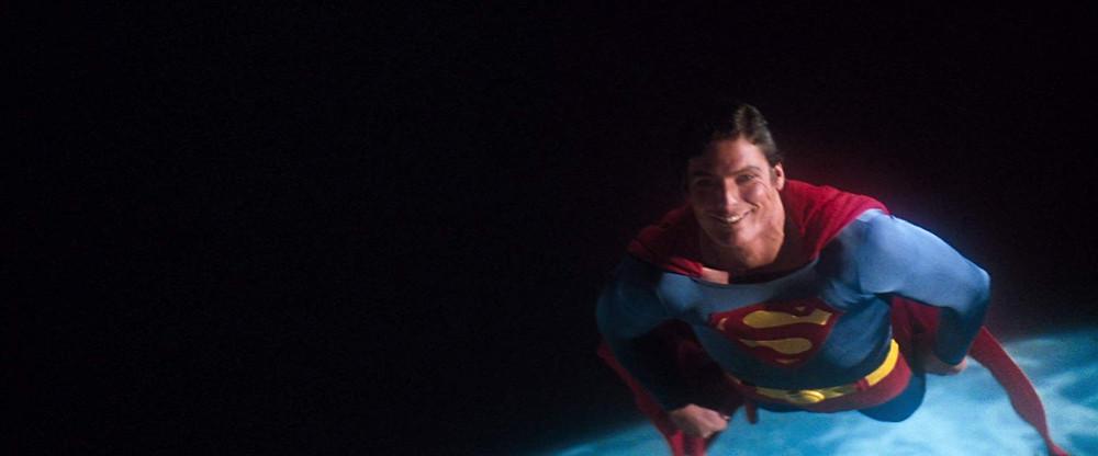 Christopher Reeve sorri em direção à câmera na cena final de Superman: O Filme (1978)