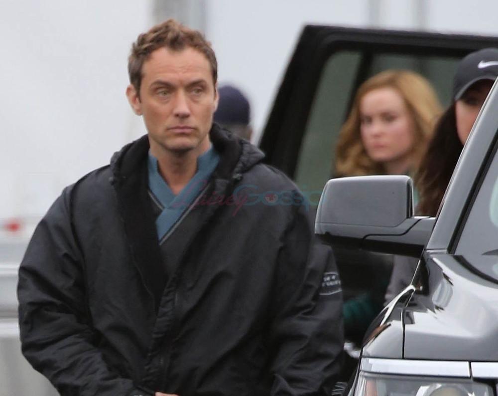 Jude Law (Capitão Marvel) no set do filme. Ao fundo desfocado, a protagonista Carol Danvers (Brie Larson).