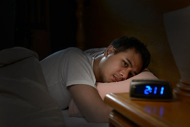 Depressed man suffering from insomnia lying in bed.jpg