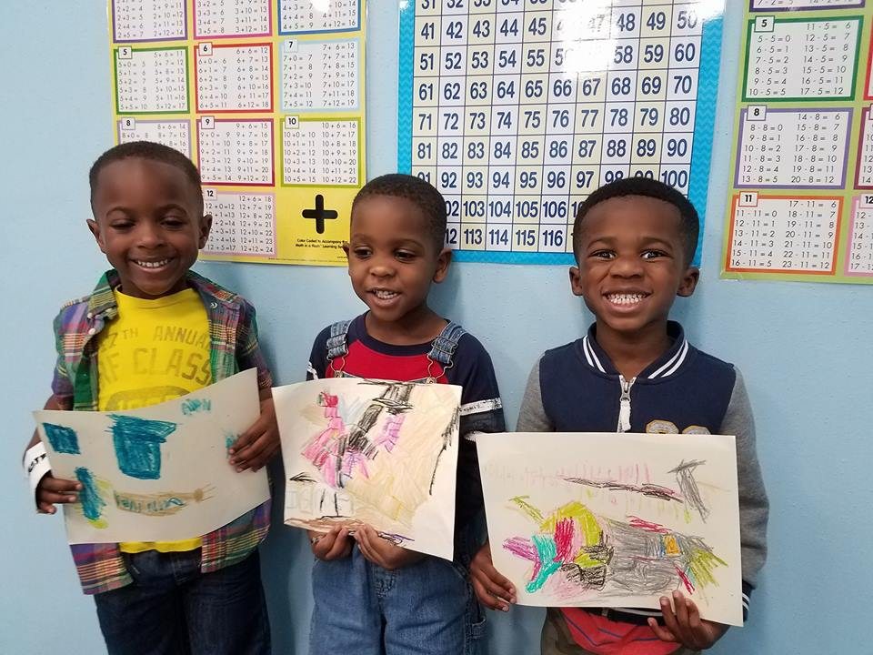 Boys smiling with artwork