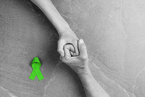 top view on hands holding green ribbon,
