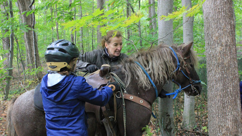 Kelly qui aide un élève avec son poney pendant le cours d'équitation