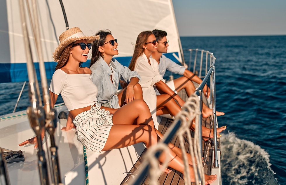 Group of friends relaxing on luxury yacht. Having fun together while sailing in the sea. T