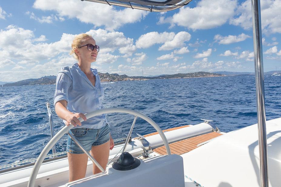 Attractive blond female skipper navigati