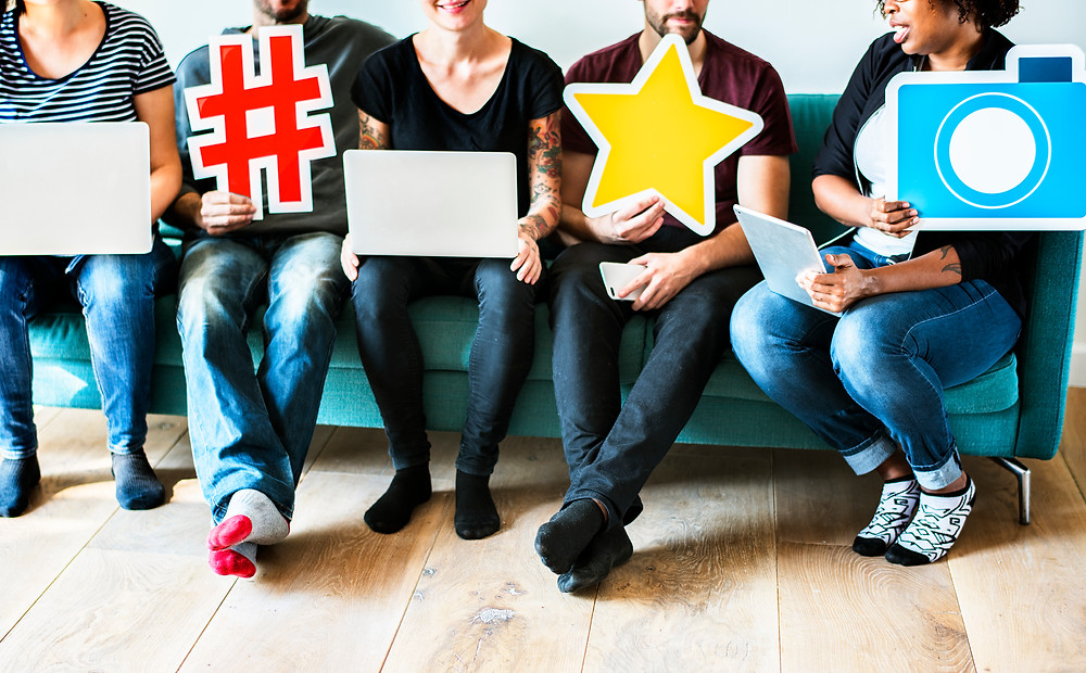 Four people sit in a row holding social media symbols including a hashtag, a star and a camera