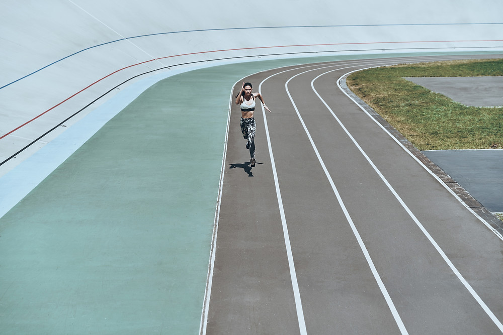 A runner sprints down a track in the sun
