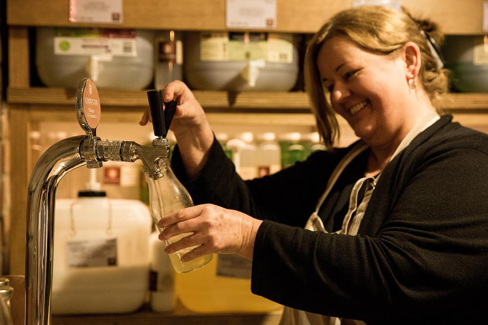 Kathy from Source Bulk Foods helping a customer refill their kombucha bottle