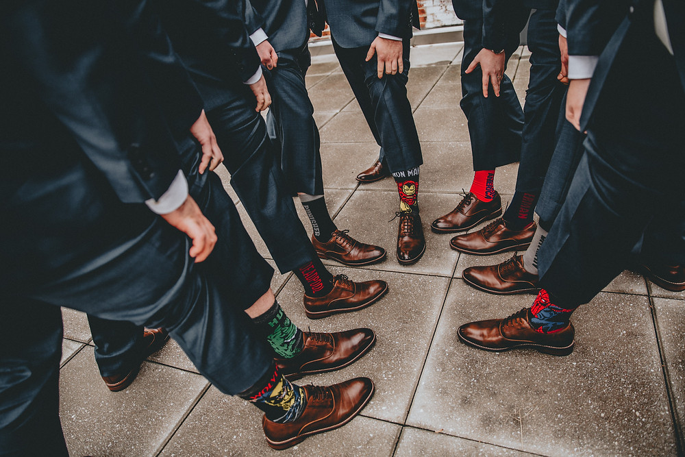 Groomsmen sharing their socks during a wedding at The Accelerator Space Baltimore