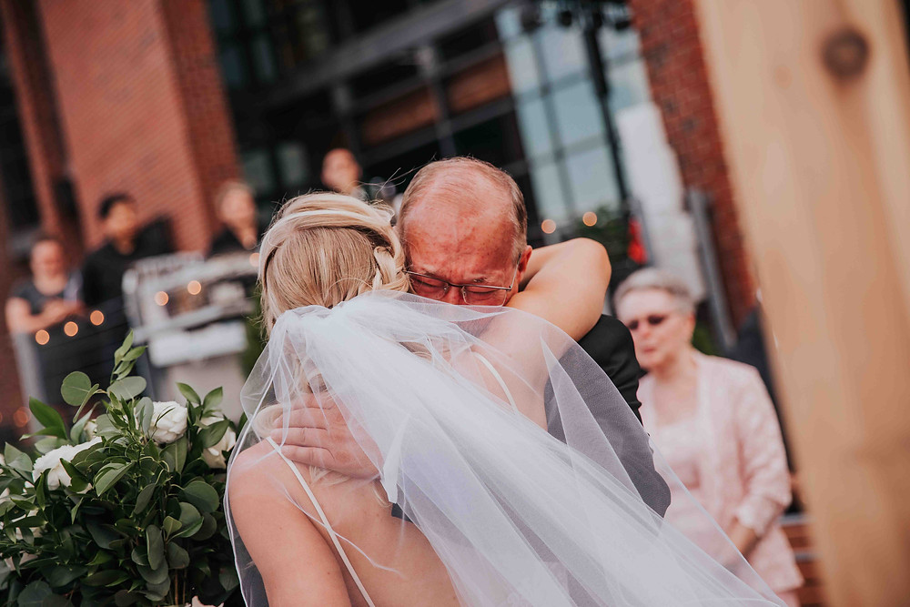 father hugging daughter on wedding day
