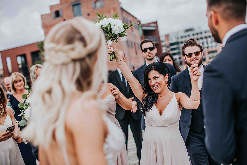 Bridesmaid excitedly putting hands in air smiling at bride