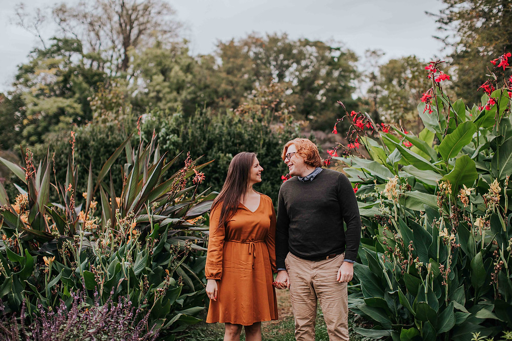 Flowers in background and woman and man holding hands in Baltimore Maryland