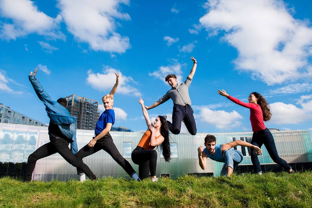 Picture of children dancing and jumping with a blue sky background