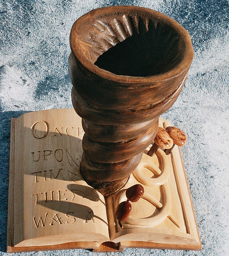 wooden sculpture of a book with a tornado and mushrooms growing out of it
