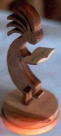small kokopelli sculpture reading