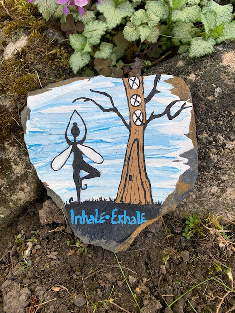 Painting on a rock of a fairy doing a yoga pose next to a tree
