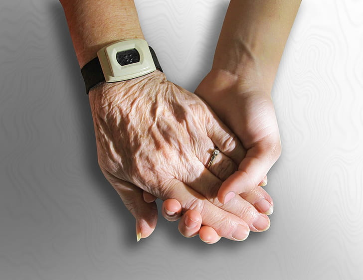 An older person's hand holding a younger adult's hand