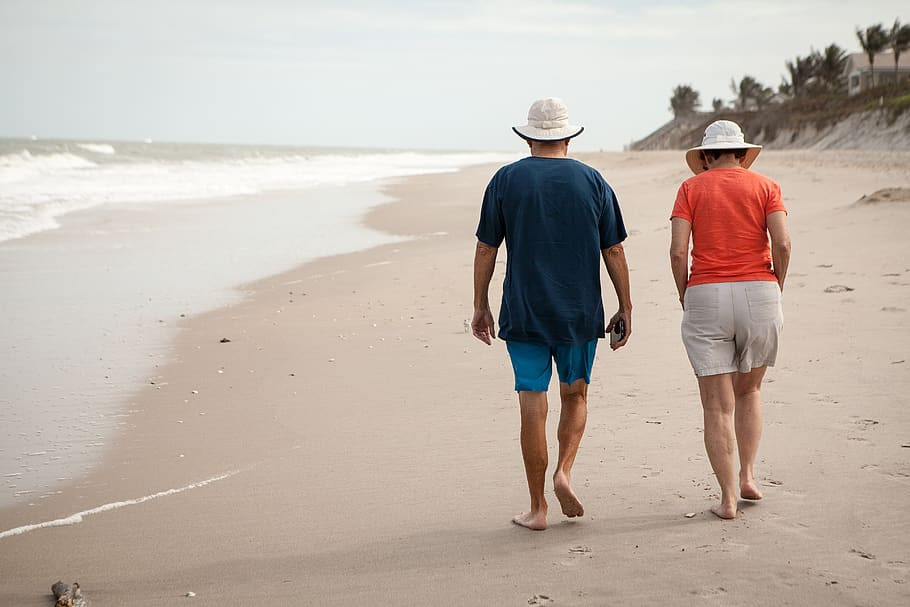An older man and woman walking down a beach together