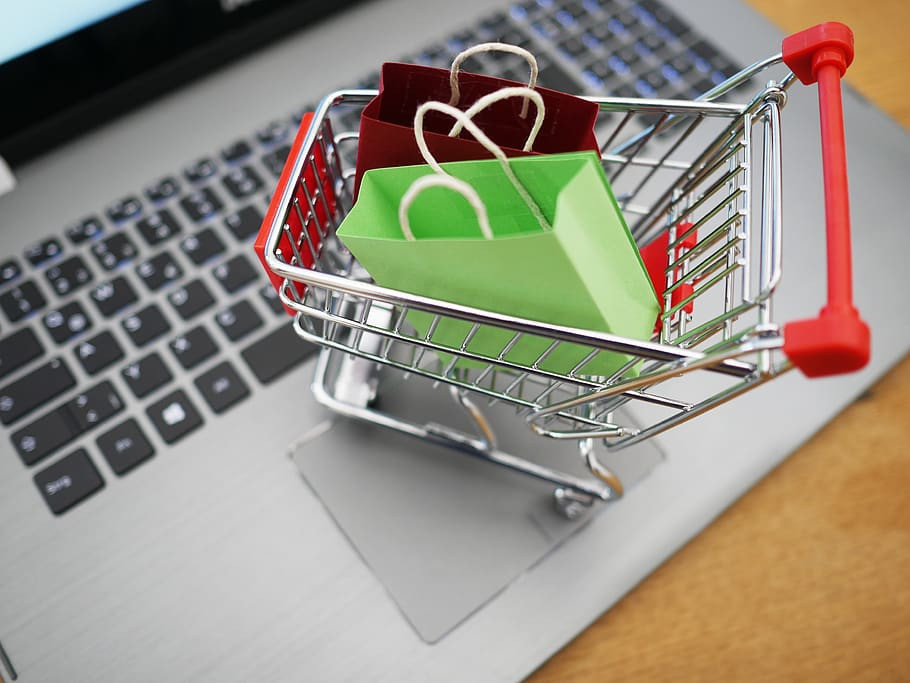 Photo of a miniature shopping cart with colourful shopping bags in it sitting on a laptop keyboard