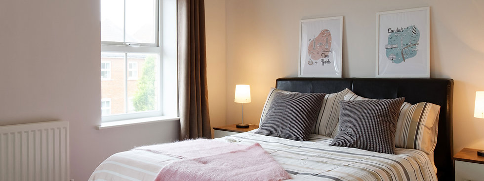 Bright bedroom with artwork on headboard