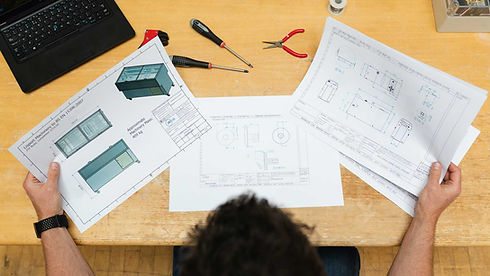 A top-down photo of a man working with schematics