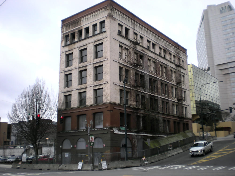 The Luzon Building in Tacoma. A tall, 6-story brick building that was built between 1890 and 1891. The bottom floor has black bricks, the second floor has red bricks, and the rest of the floors have white bricks, crowned with a trimming of red at the top. It is abandoned, with notable staining on the bricks. The building itself has barriers and fencing all around it for safety precautions, because the building is threatening to lean and collapse from neglect.